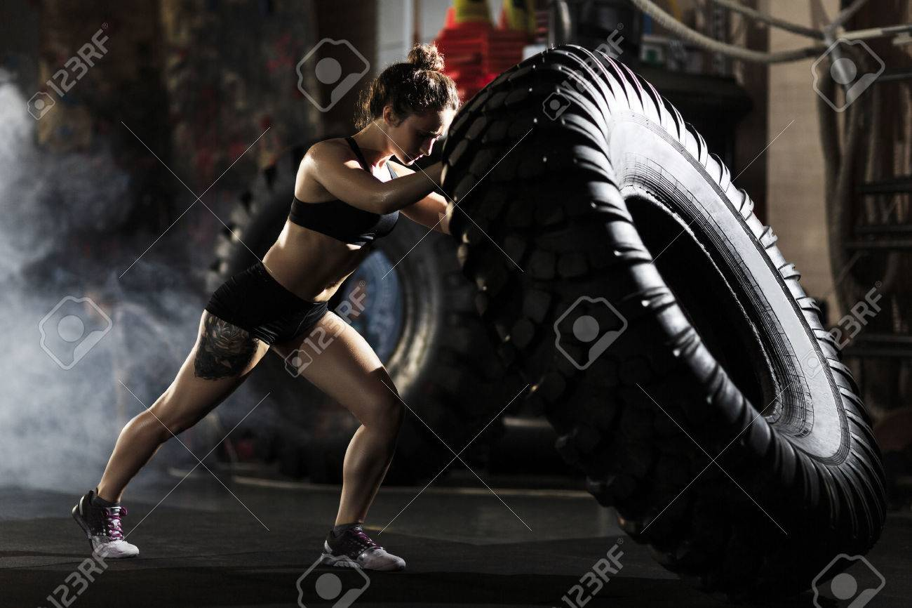 Strong fit woman flipping tire in gym - 59969620