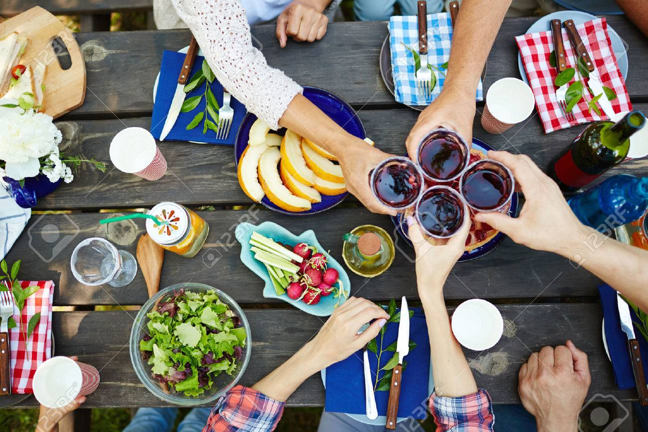 Hands with red wine toasting over served table with food Standard-Bild - 60144215
