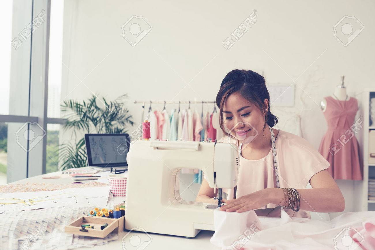 Smiling fashion designer using sewing machine and sitting behind her desk Standard-Bild - 64831687
