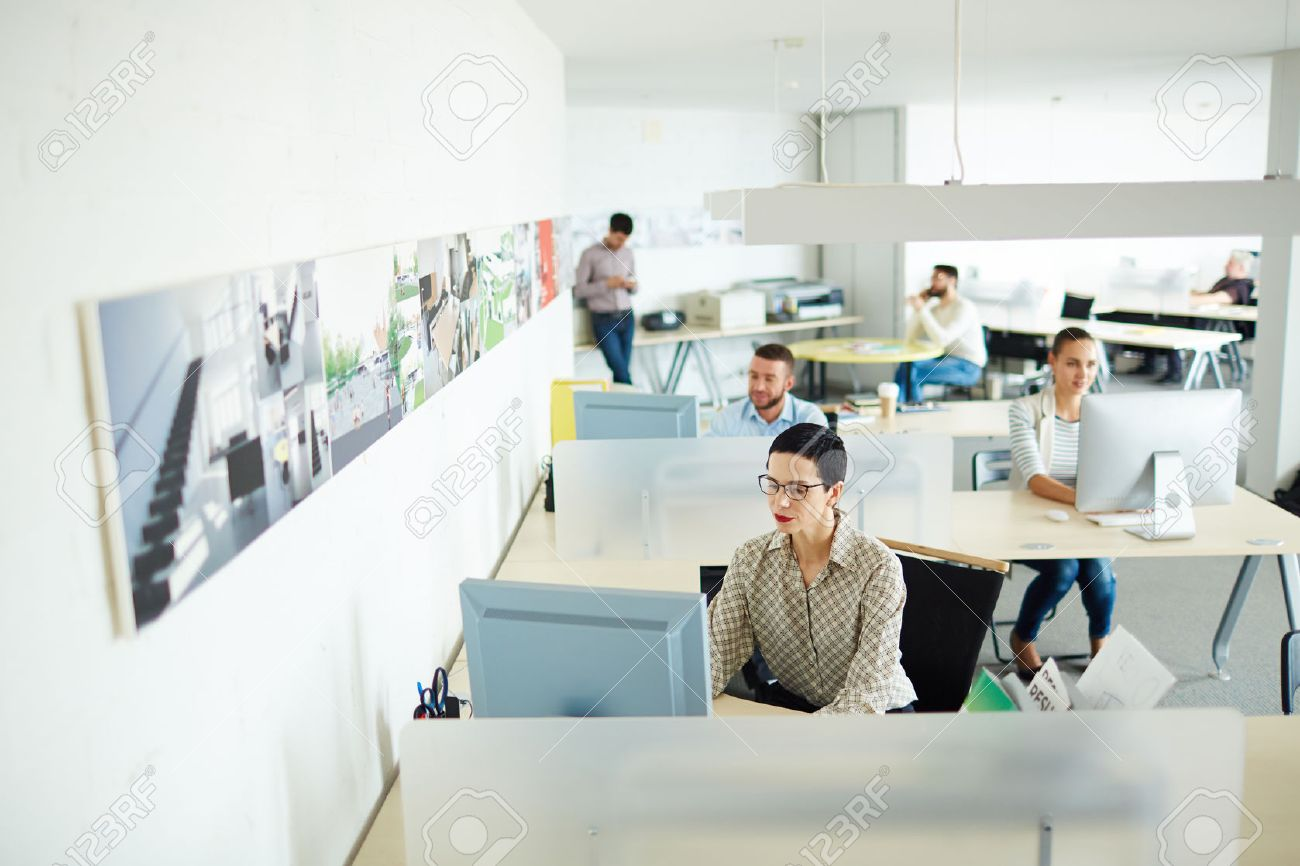 Contemporary businesswoman computing by her workplace in open space office Stock Photo - 60414404