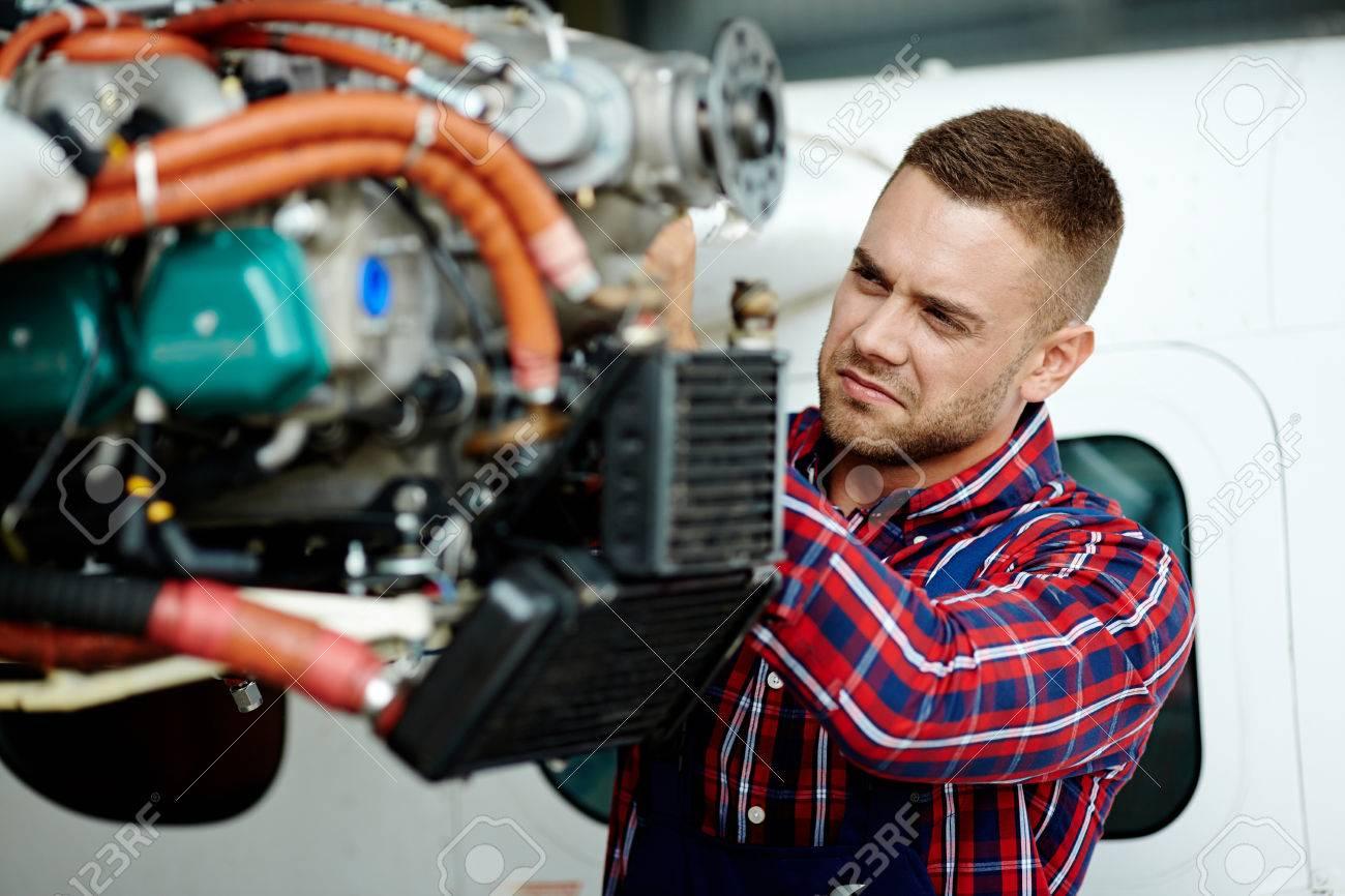 Young engineer repairing part of airplane Standard-Bild - 60799016
