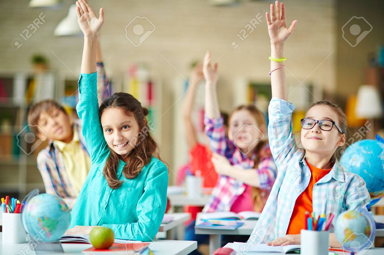 Intelligent group of school children raising their hands in to answer a question Standard-Bild - 60799108