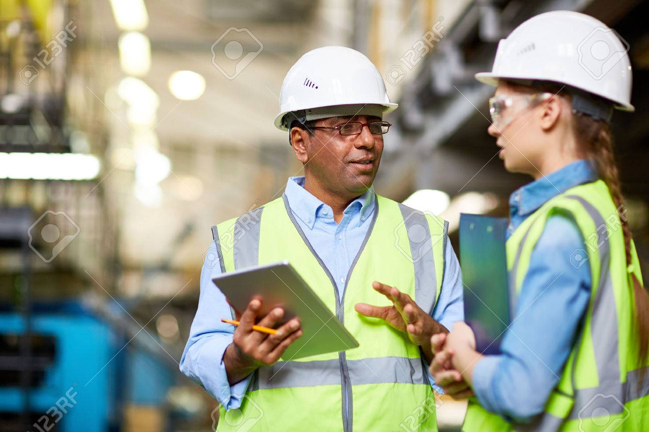Two engineers discussing work and using tablet pc Standard-Bild - 61866670