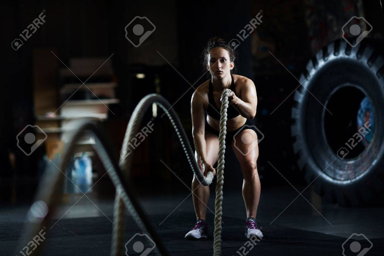 Sporty woman practicing exercise with battle rope Standard-Bild - 61941207