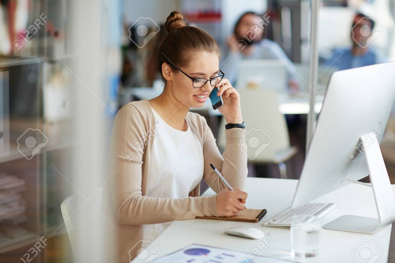 Young professional businesswoman working in public relations talking on phone with partners making notes in small notebook, sitting at computer desk in modern office space Standard-Bild - 62735323