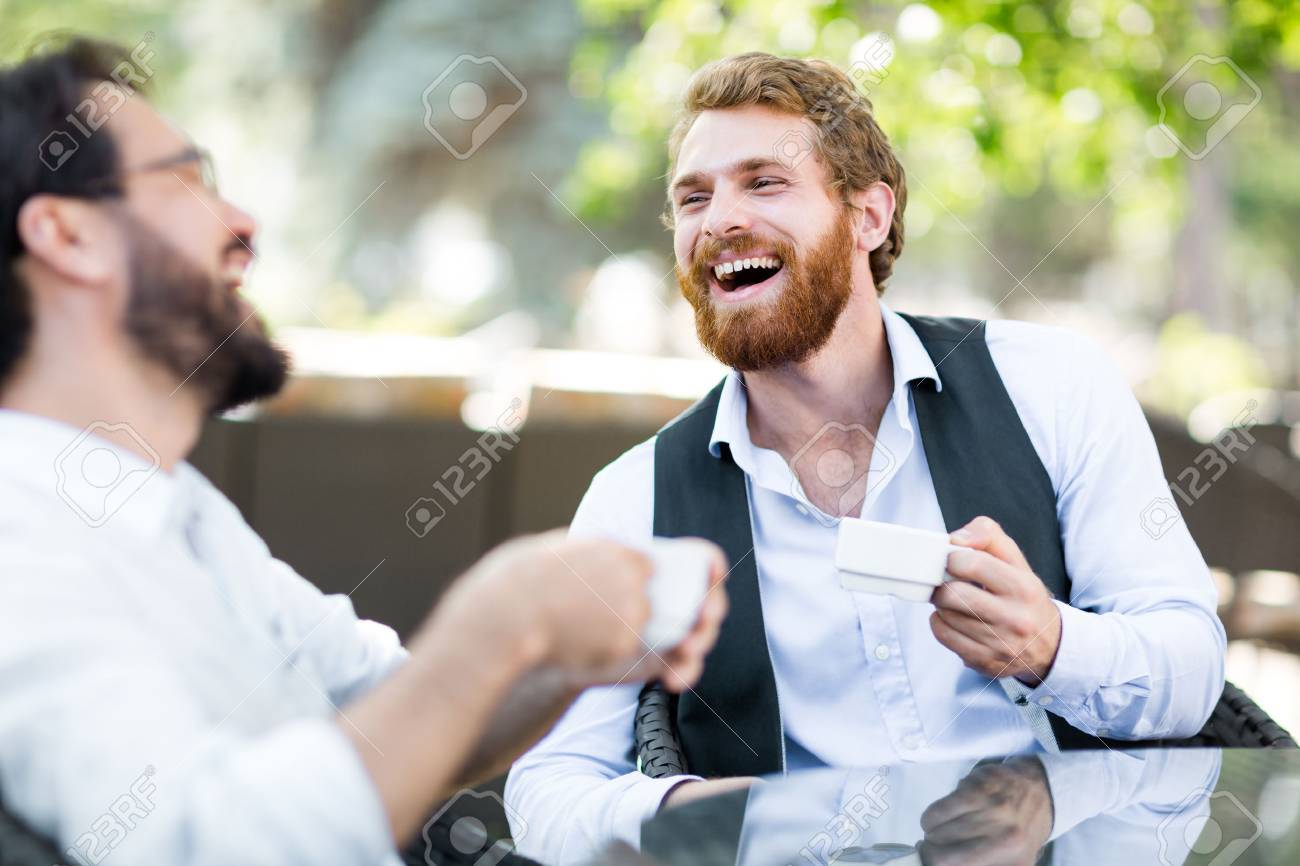 Friendly young men with coffee talking in outdoor cafe Standard-Bild - 62864103