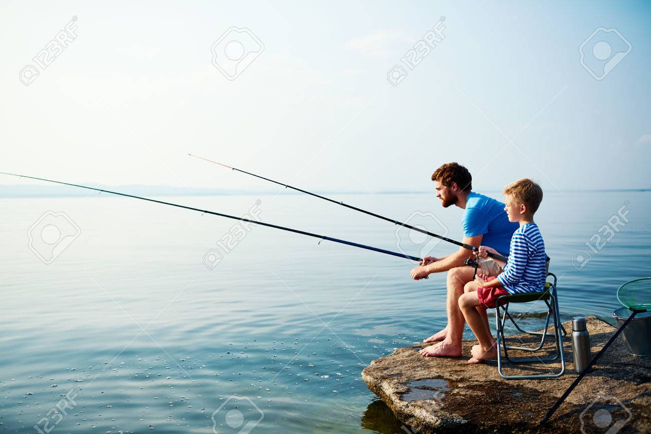 Young man and little boy fishing together - 62864639