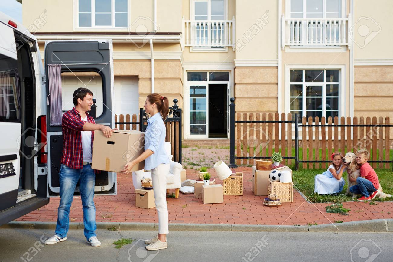 Young man giving his wife box while unloading things from van Standard-Bild - 65130643