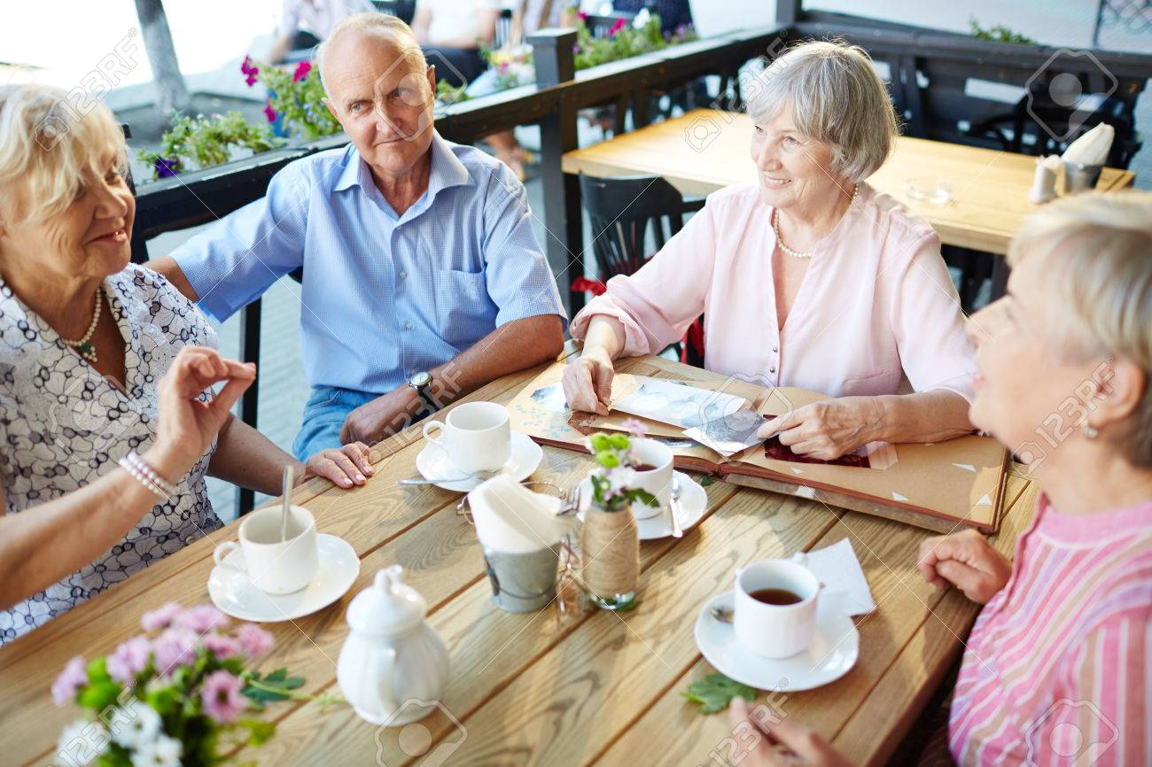 Seniors gathered by table for tea and talk Standard-Bild - 63745676