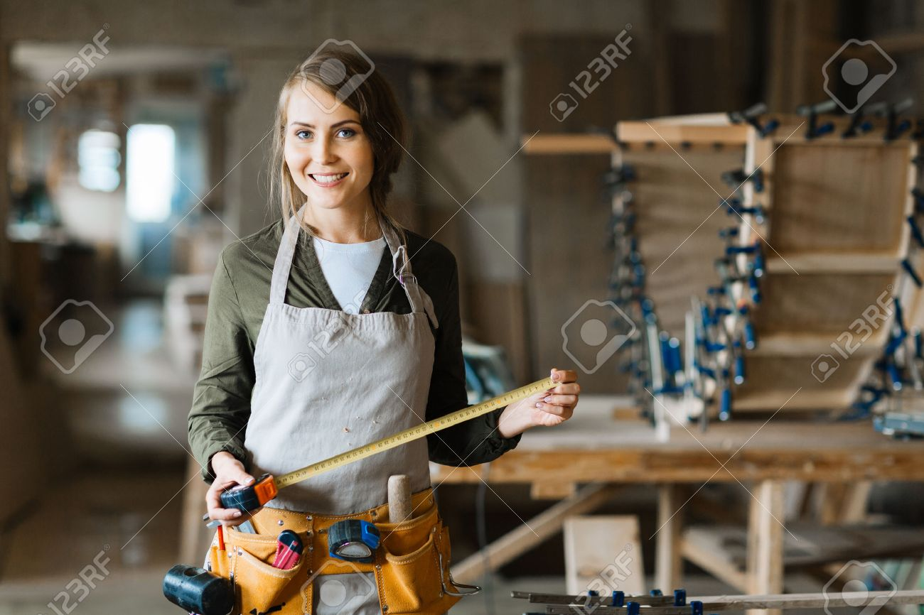 Young plumber with tool-belt and tape-measure looking at camera Standard-Bild - 63745705