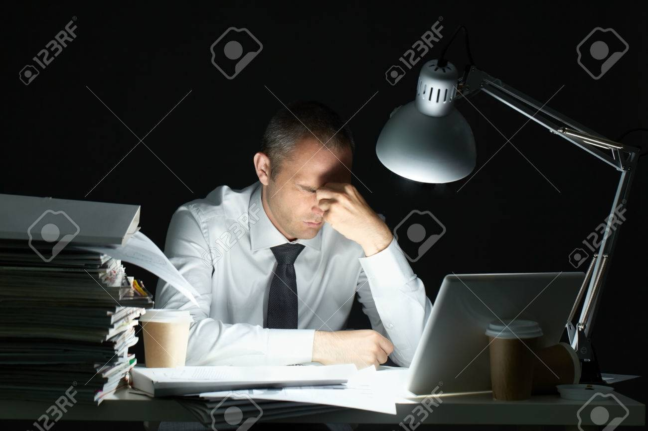 Businessman sitting at office desk full with papers being overloaded with work Standard-Bild - 63746030