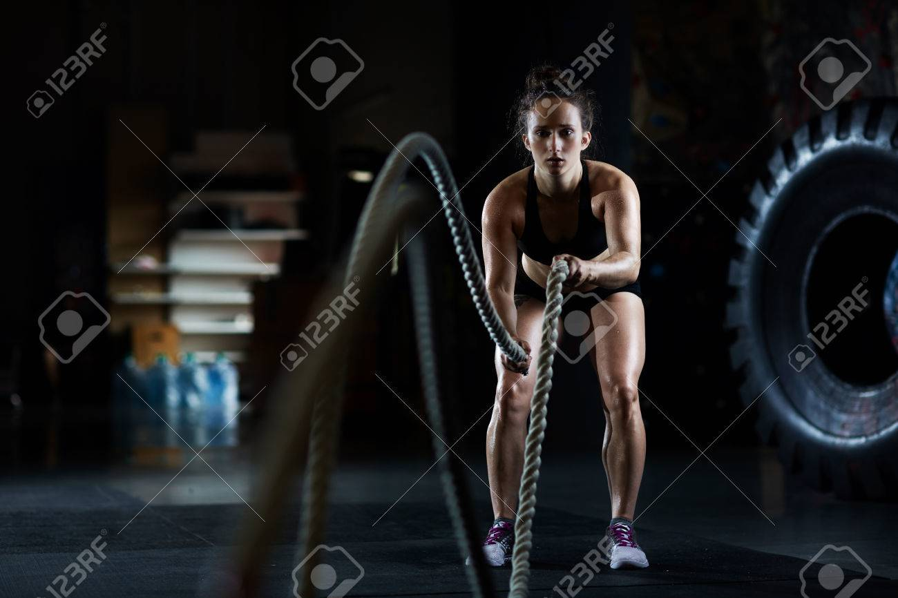Young woman doing battle rope exercises in gym - 63442494