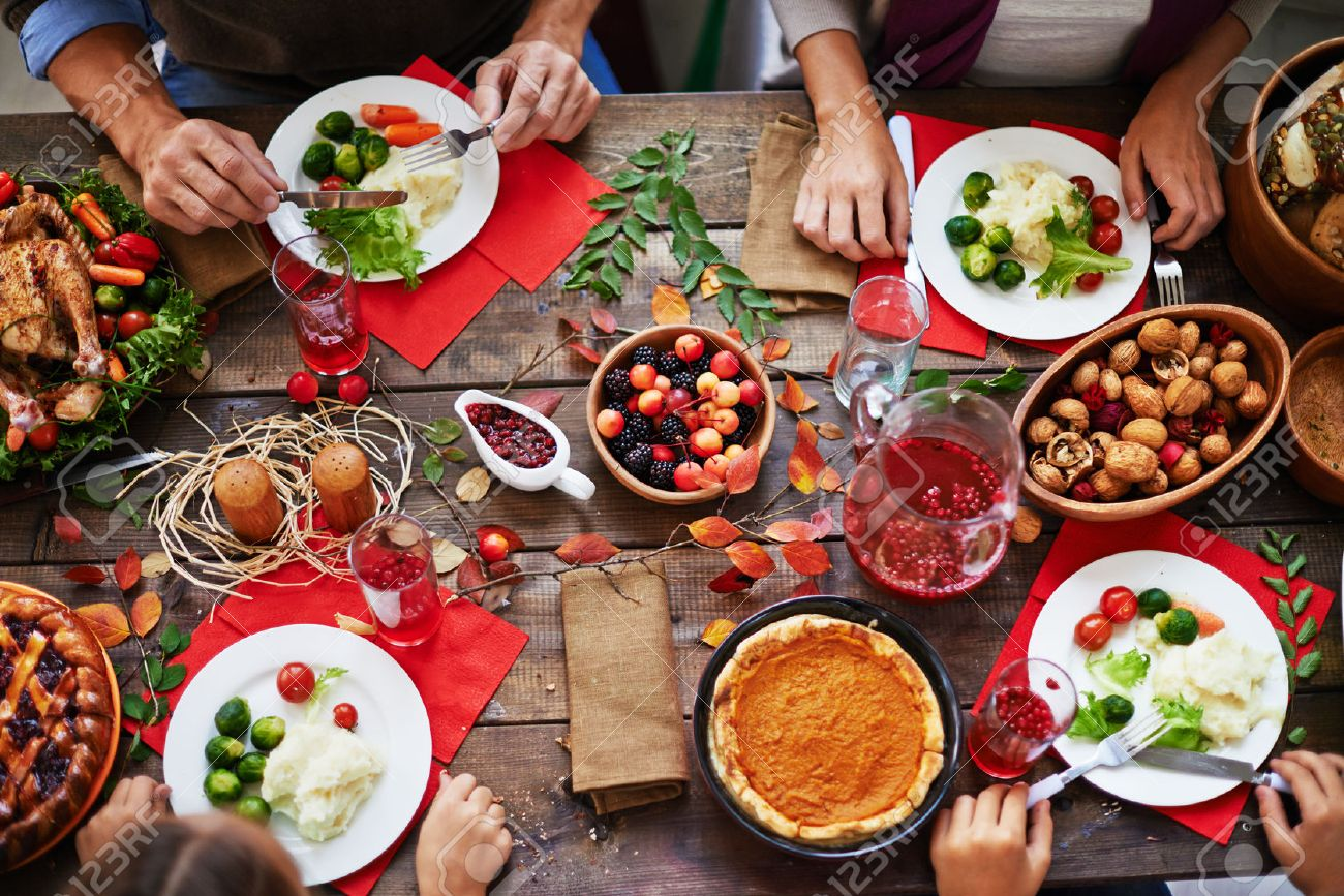 Above view of thanksgiving dinner and family eating at table - 63746701