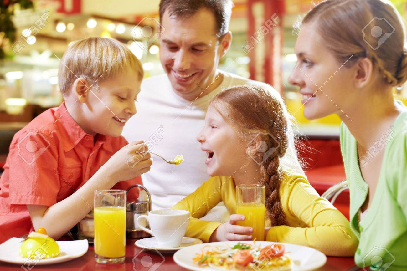 Family with two children sitting in cafe, the boy feeding his sister with spoon Standard-Bild - 64024628