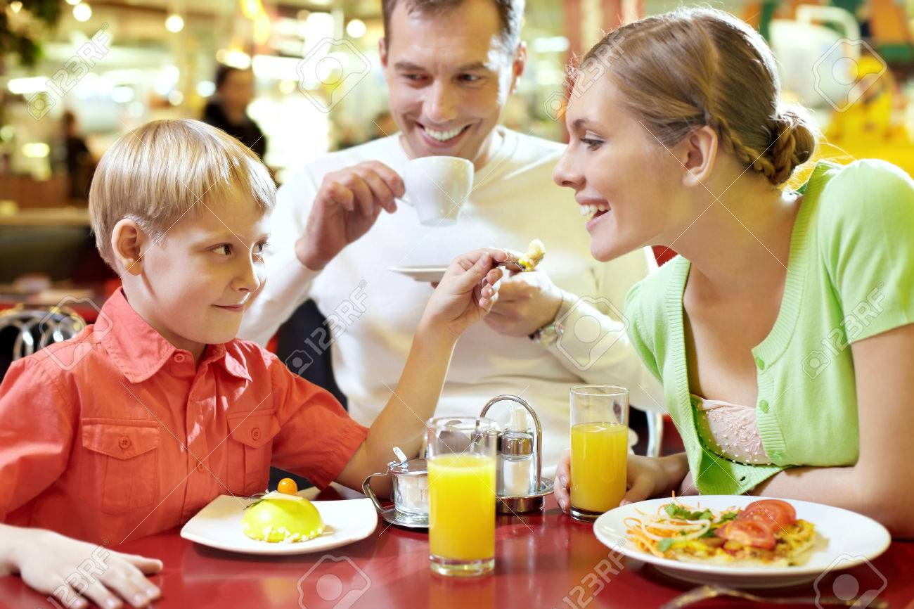 Family with one child sitting in cafe, the boy feeding his mother with spoon Standard-Bild - 64024629