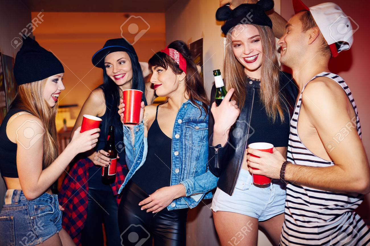 Cool students hanging out drinking beer and talking in corridor of big private house at swag party - 65133672