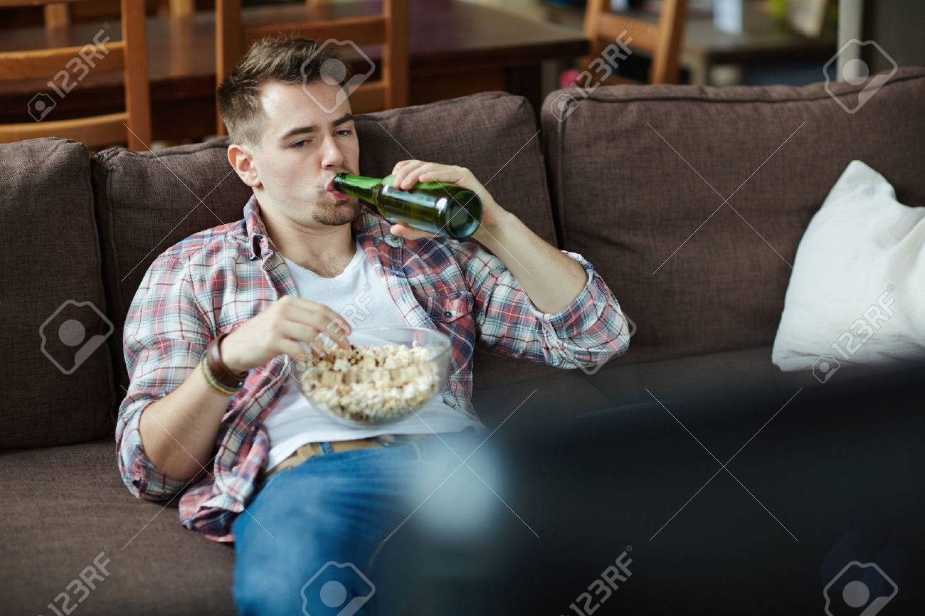 Un Jeune Homme Paresseux Boire De La Bière Et Manger Du Pop-corn Devant Le  Téléviseur Banque D'Images Et Photos Libres De Droits. Image 65134609.