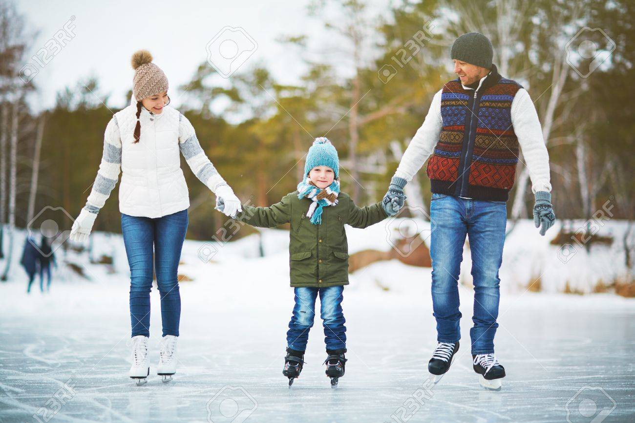 Family portrait of cheerful young parents looking at their son with smile and holding his hands while skating on winter park rink, blurred background Standard-Bild - 65871189