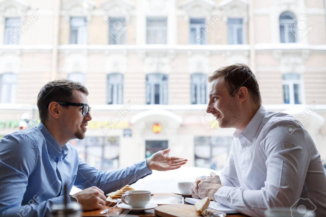 Young entrepreneurs talking at lunch break in cafe Standard-Bild - 65996480