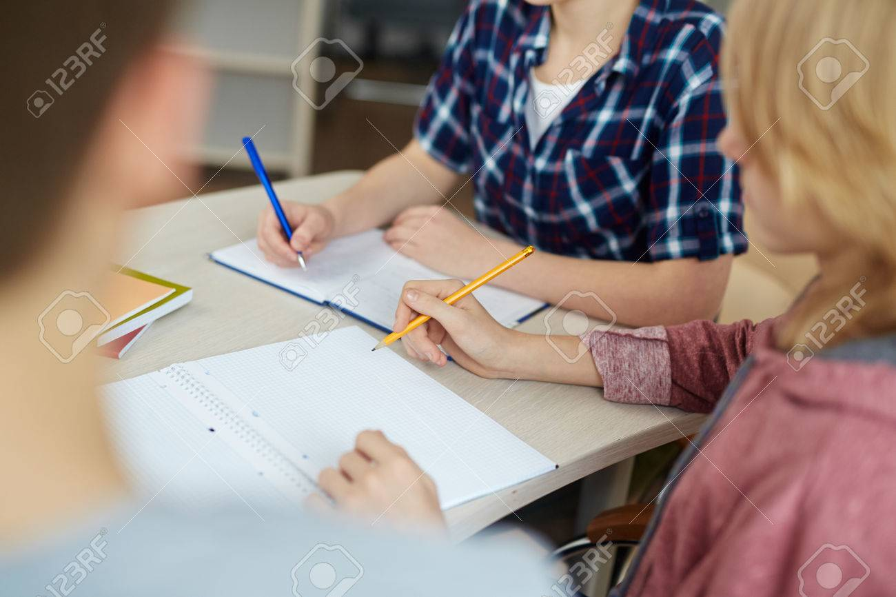 Group of students making notes or drawing sketches in copybooks