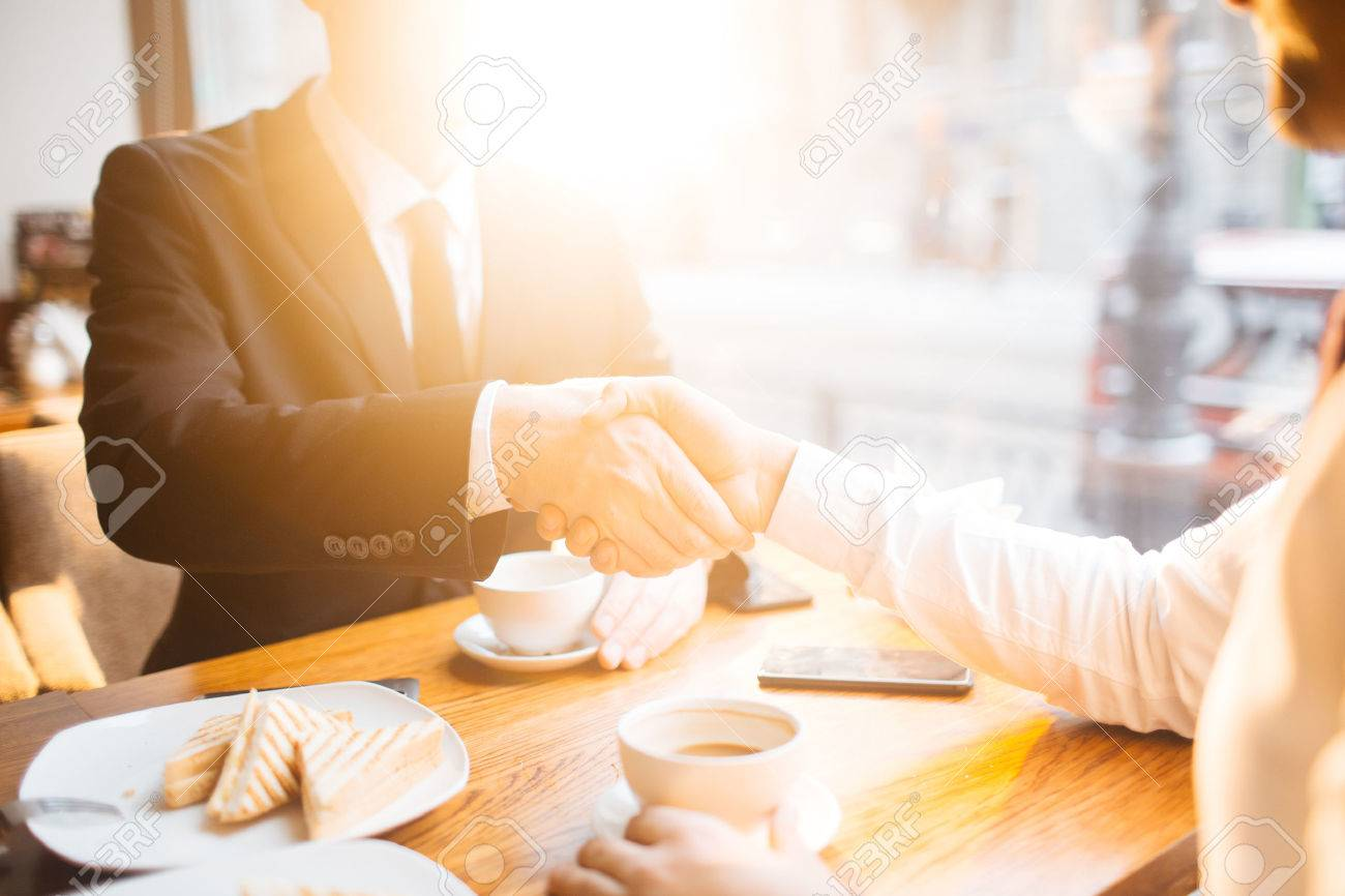 Businessmen handshaking in cafe during lunch - 67405384