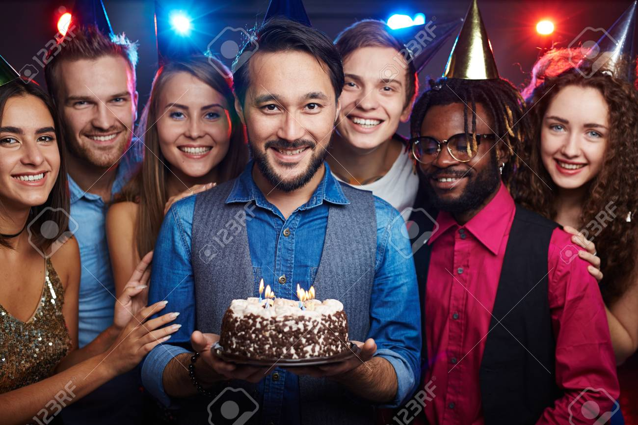 Attractive Asian Man Holding Birthday Cake With Burning Candles Among His Intercultural Friends Stock Photo