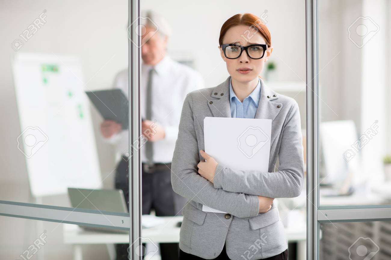 Scared employee with documents standing by door of her boss office and going to talk to him - 93743688
