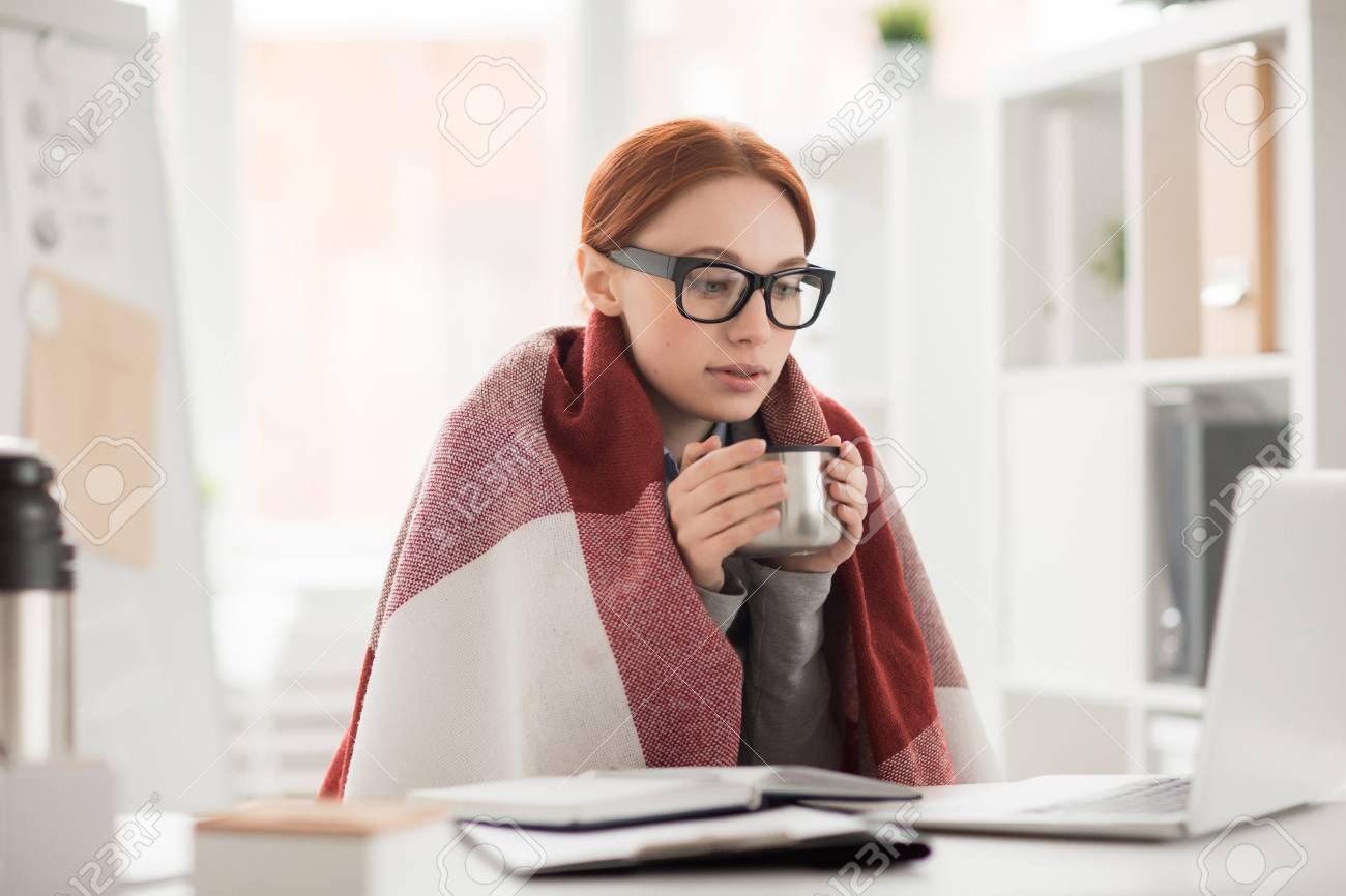 Young woman in plaid and eyeglasses drinking hot tea from mug during work in office - 93756831