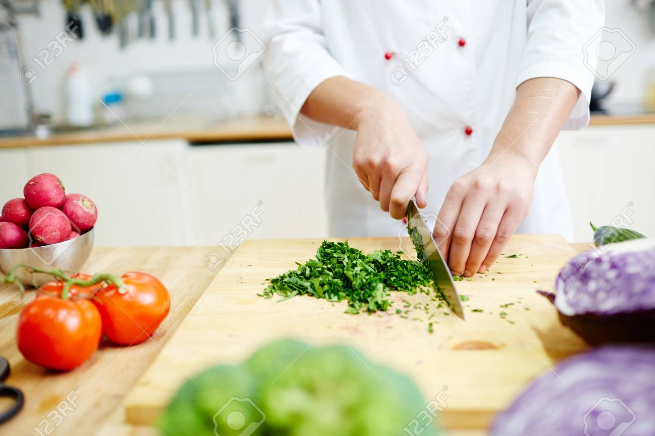 Chef Cutting Greenery On Wooden Board In The Kitchen While Cooking ...