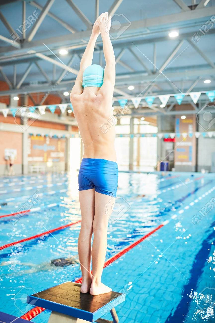 Boy in swimwear going to dive into water of swimming-pool from..