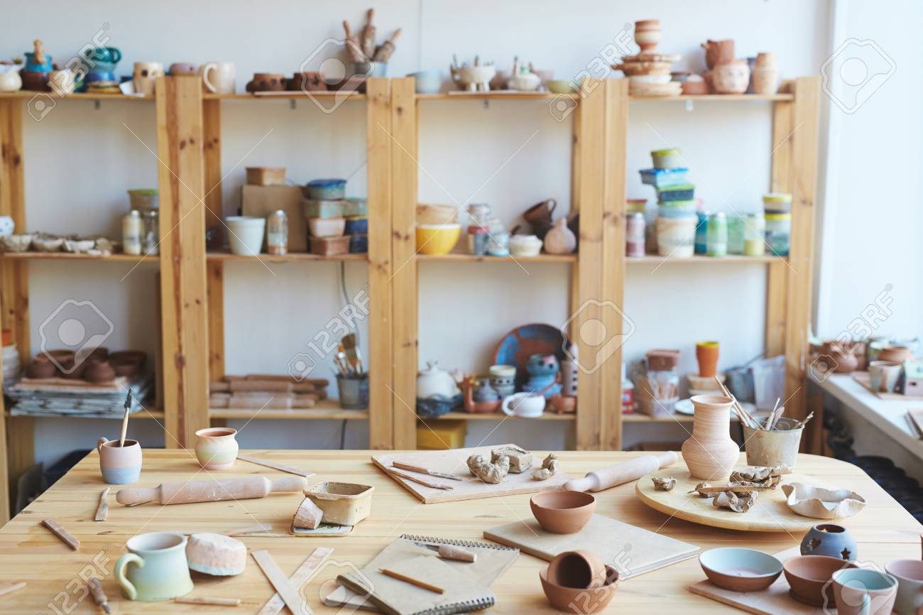 Messy workshop with handmade clay vases, pots and jars made by professional potter - 100143230