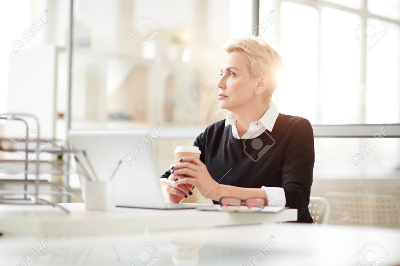 Thoughtful middle-aged businessman enjoying delicious cappuccino and looking out window while taking a break from work, interior of modern office on background - 102312020