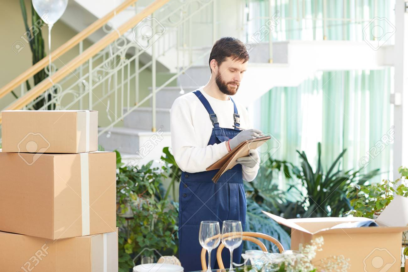 Moving company foreman writing information about delivery - 103103309
