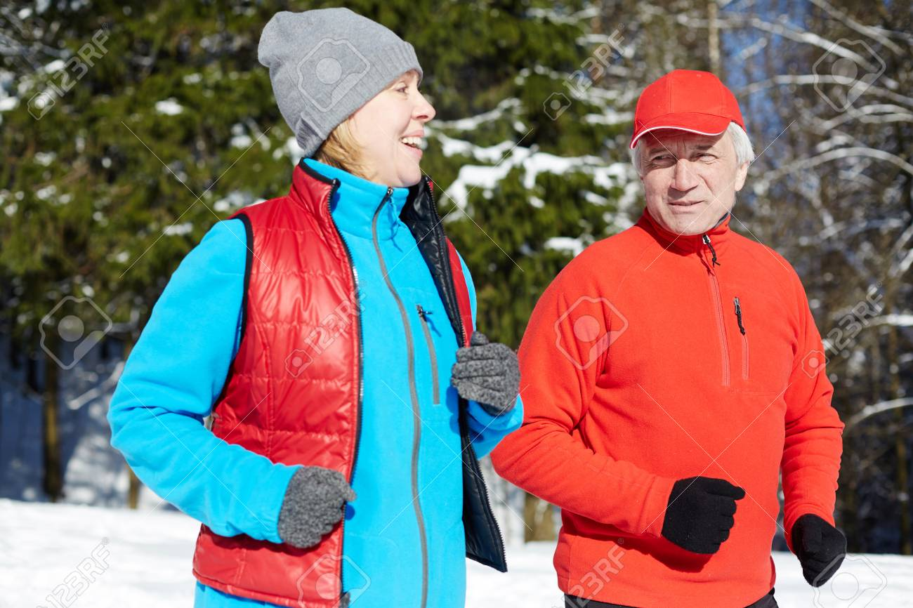 Happy mature sporty couple in activewear jogging in winter forest in the morning - 110665521