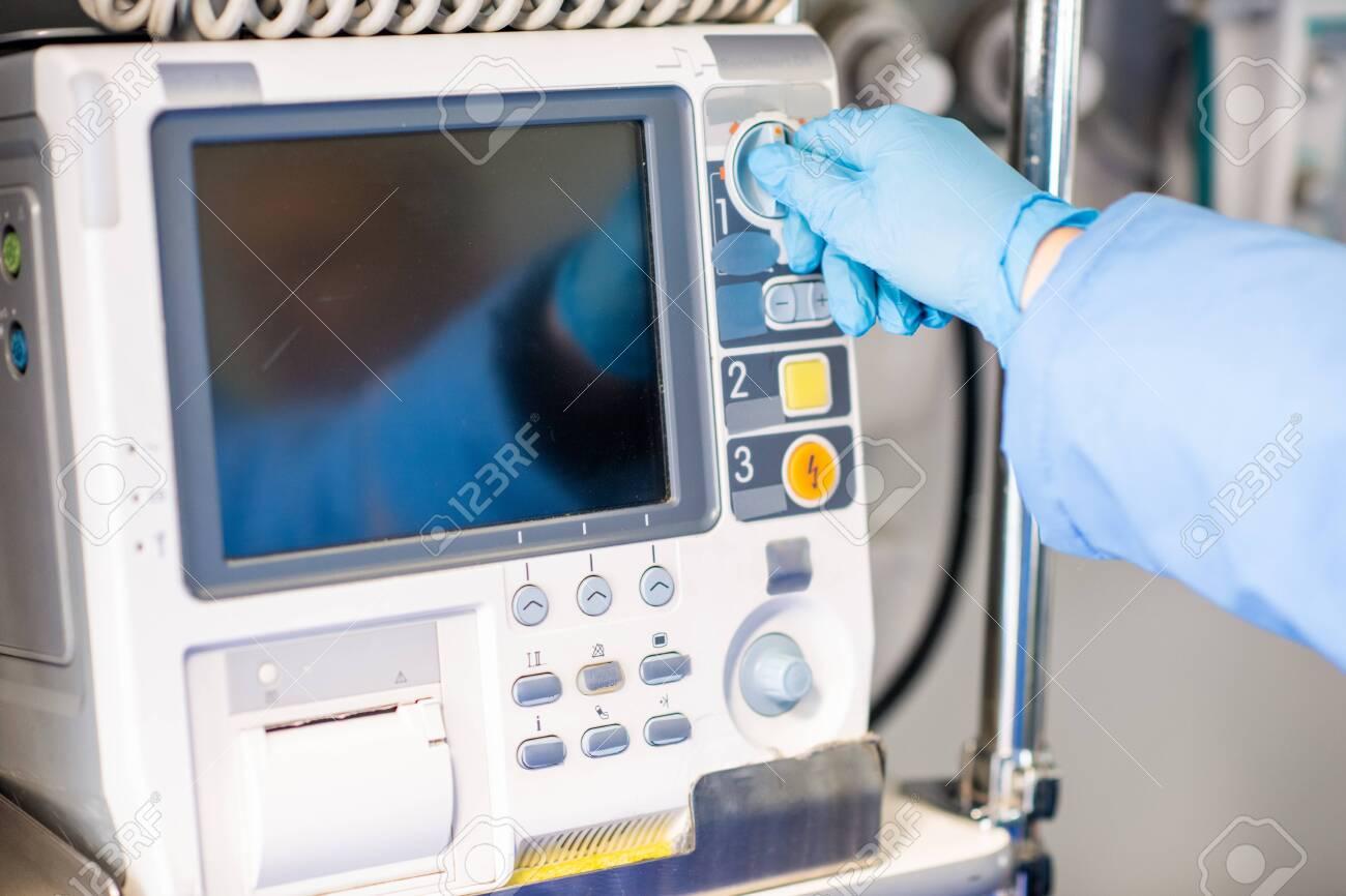 Paramedic in gloves adjusting medical first aid equipment inside ambulance car - 133946769