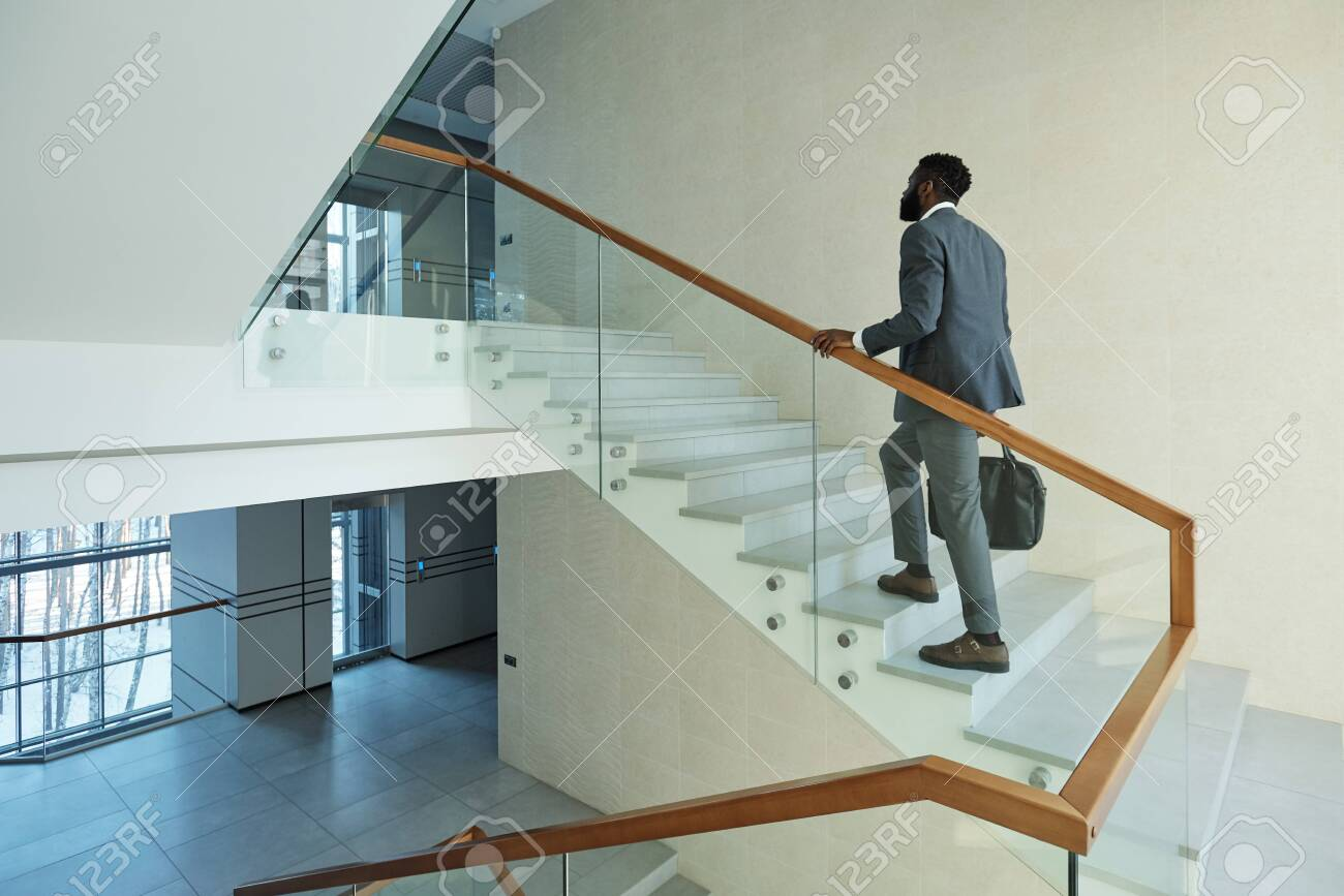 Young elegant African businessman with black leather handbag going upstairs to his office inside business center - 138185140