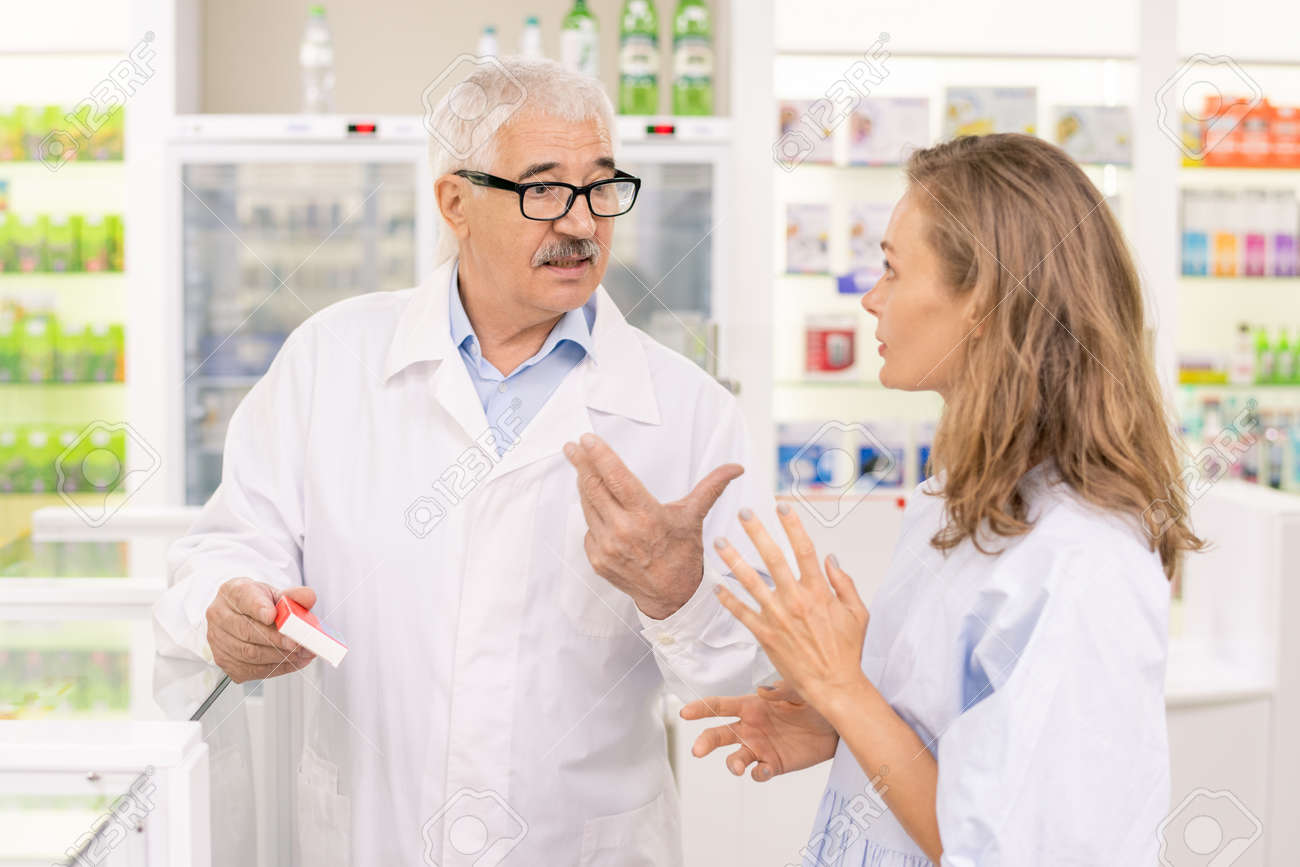Senior male pharmacist holding new medicaments while consulting his assistant - 155627611
