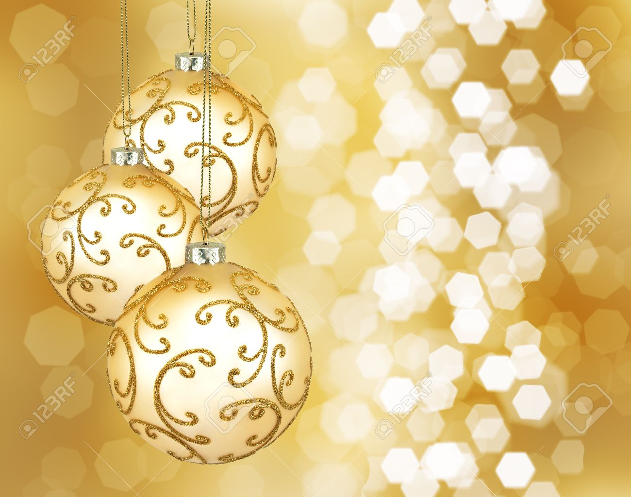 Three beautiful golden christmas balls on a golden background - 15410593