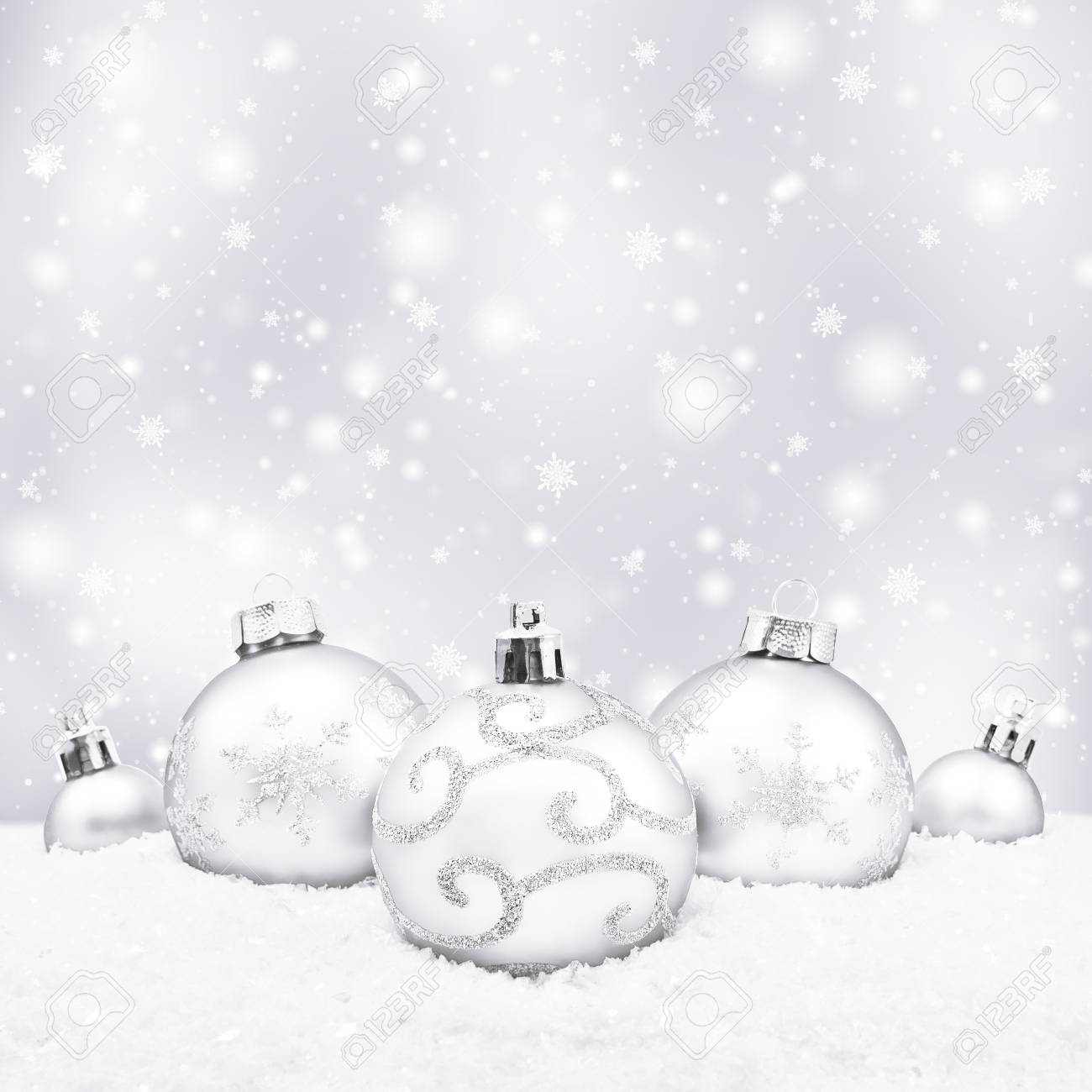 White Christmas Background.Five White Christmas Balls On Silver Background