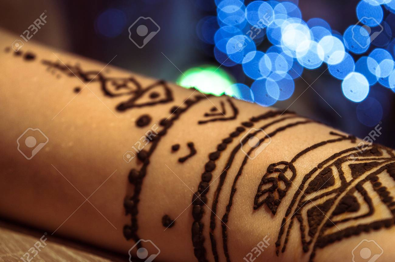 Close Up Of A Hand Drawing Fake Tattoo With Henna Paint