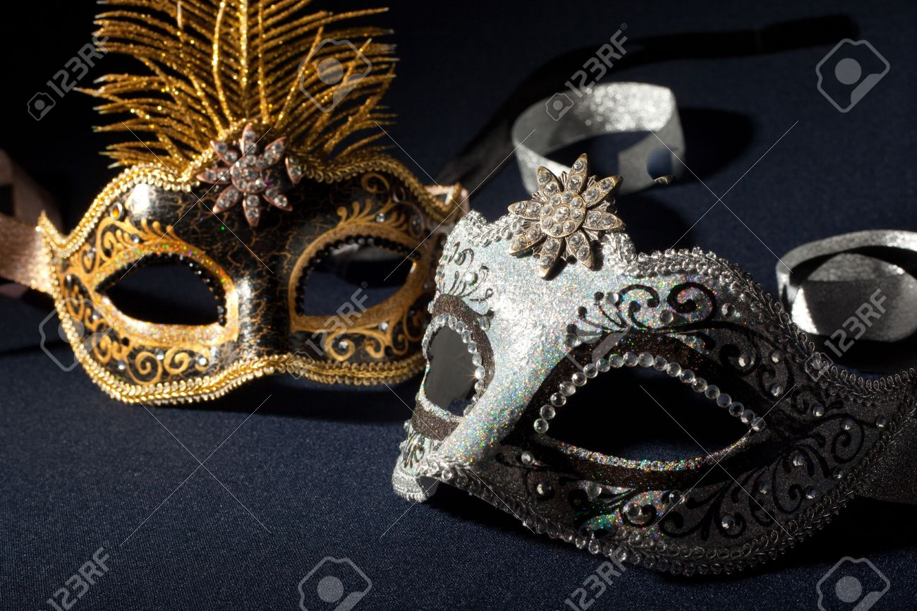 silver and black carnival masks isolated on a black background stock