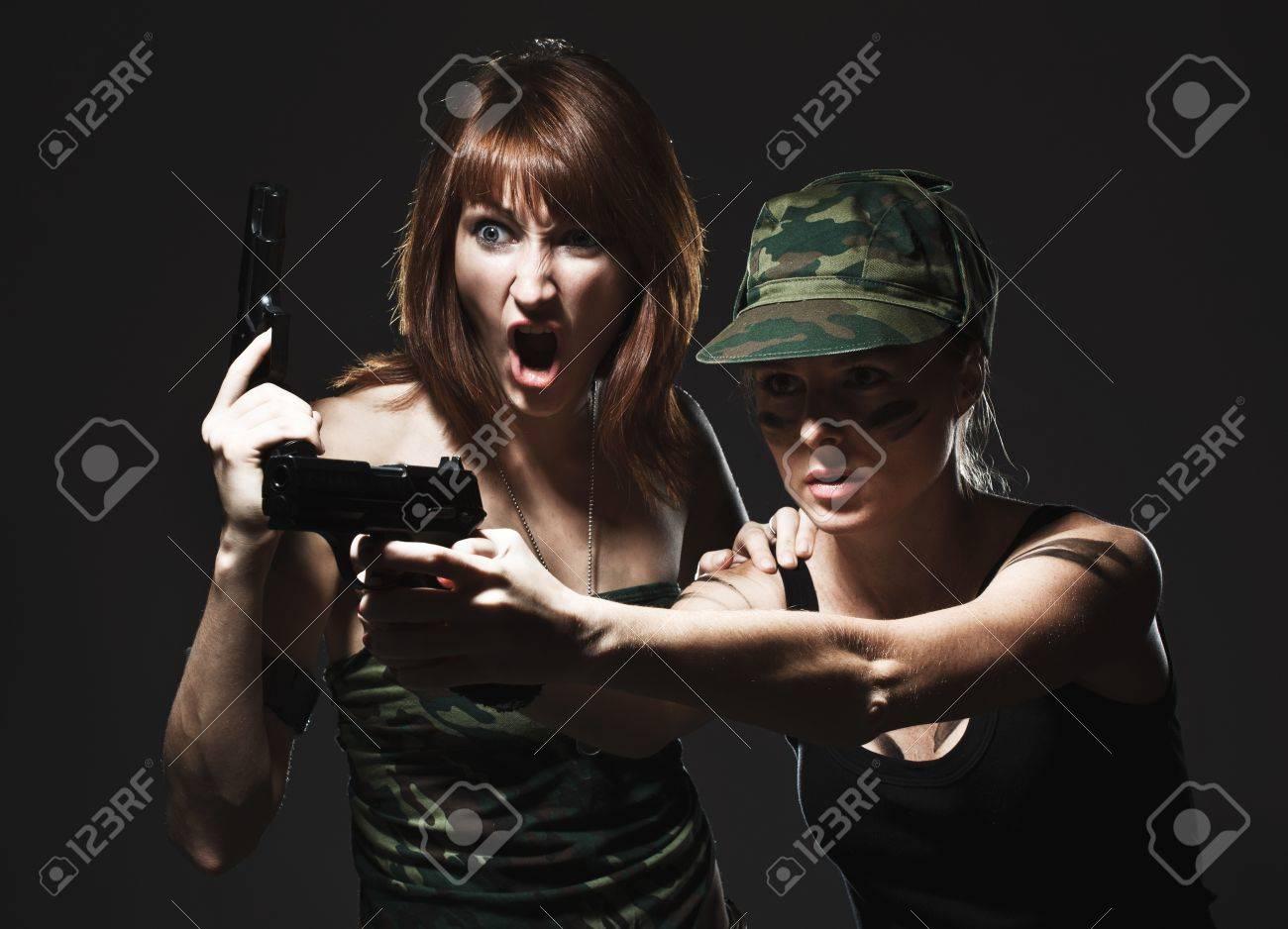 Sexy women holding gun on gray Stock Photo - 12184446