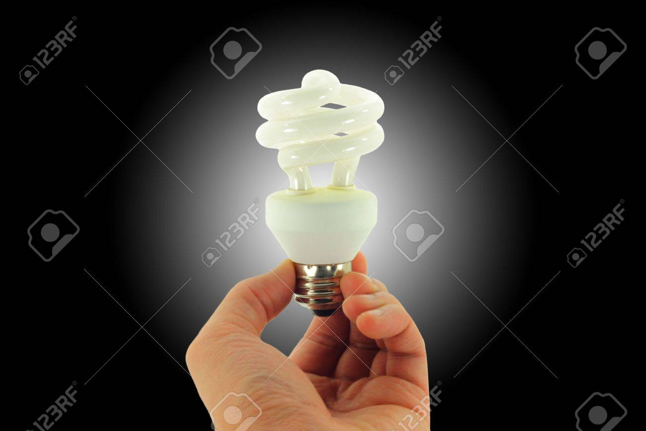 Compact Fluorescent Light bulb held in hand isolated on a black background with a white spotlight - 4019546