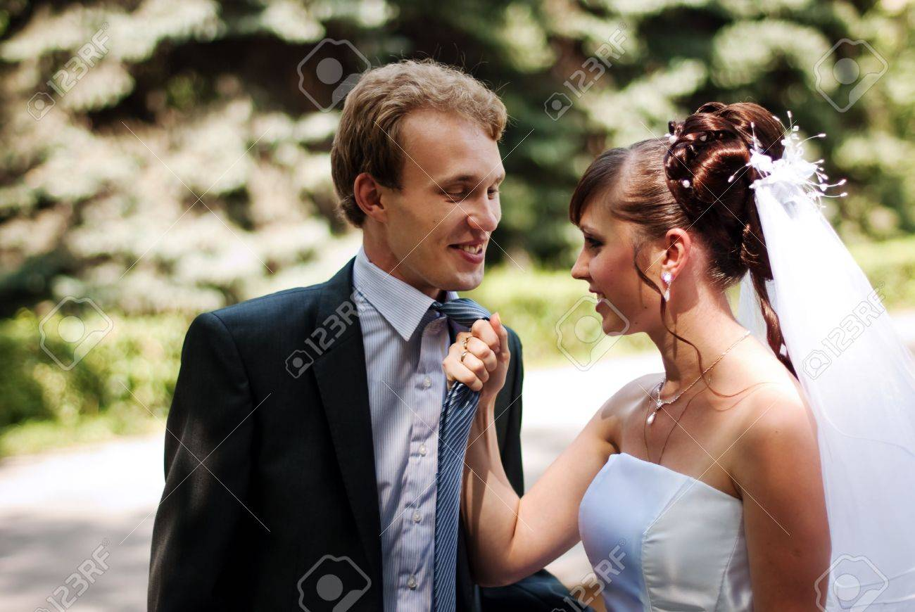 Beautiful and young married couple in the park, wife caught her husband for a tie Stock Photo - 7581035
