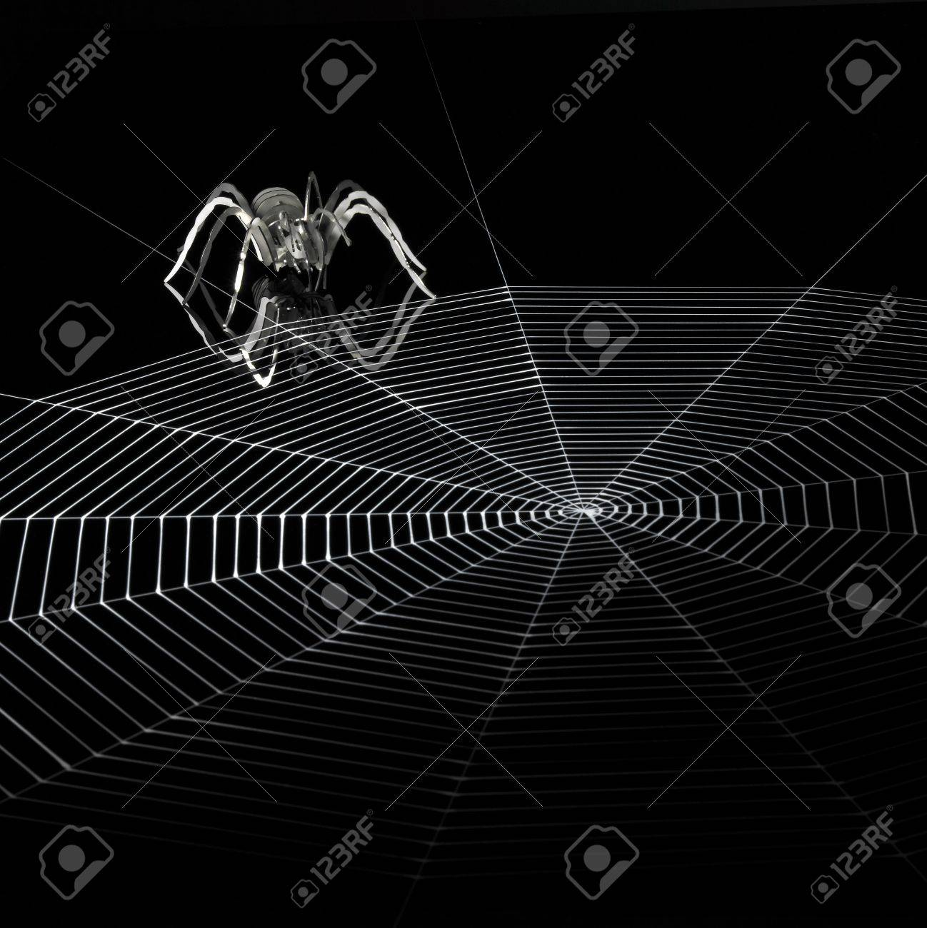 a simplified spider made of metal and a artificial spiderweb. Red illuminated studio shot in black back Stock Photo - 10916596