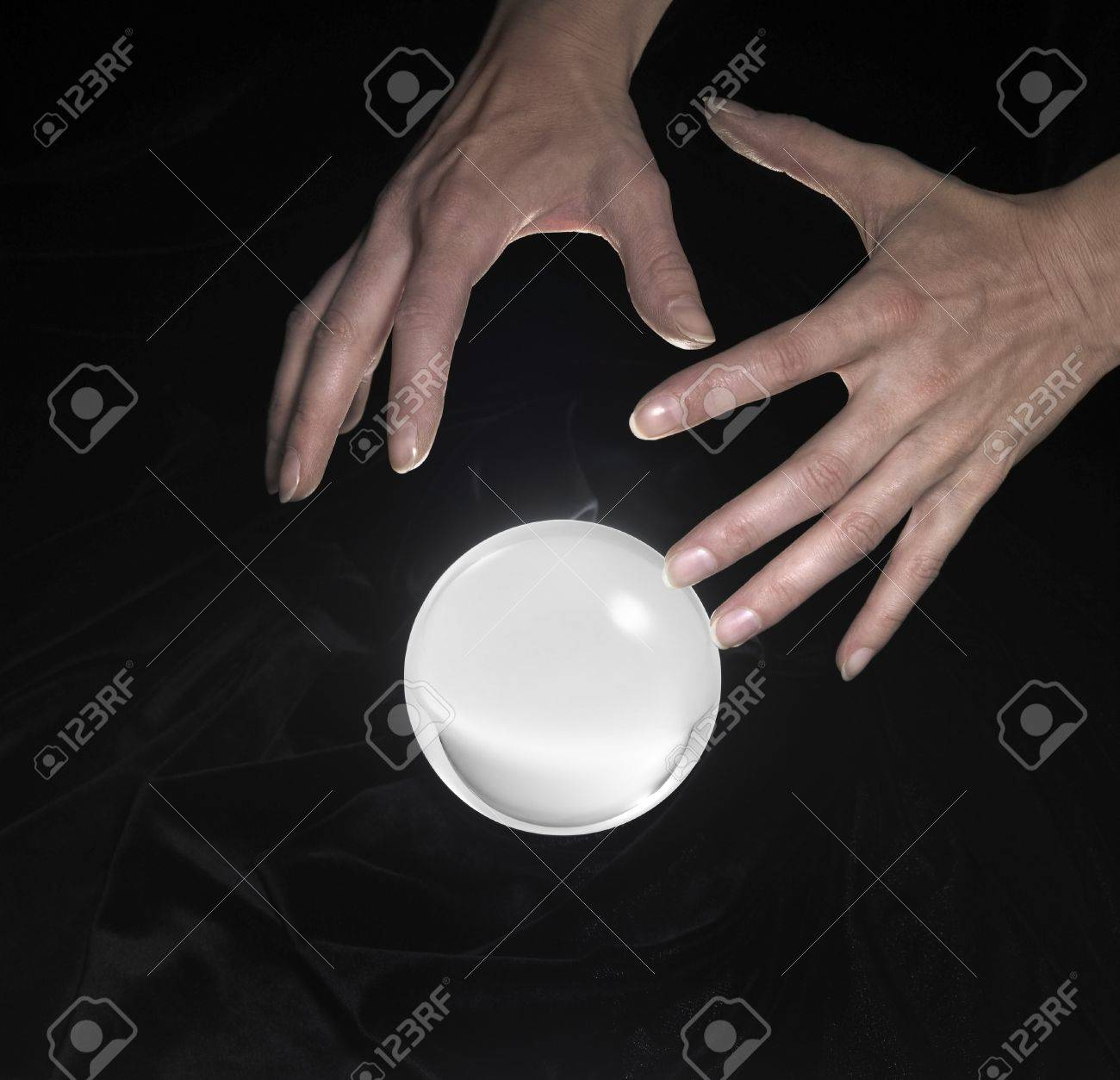 high angle shot of a glowing crystal ball surrounded by black crinkly fabrics and two hands around Stock Photo - 10985358