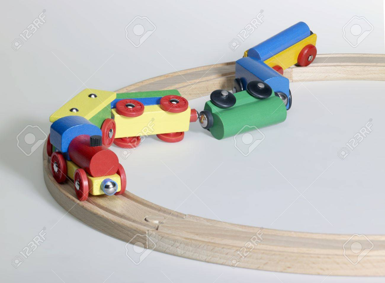 studio photography of a colorful wooden toy train on wooden tracks..