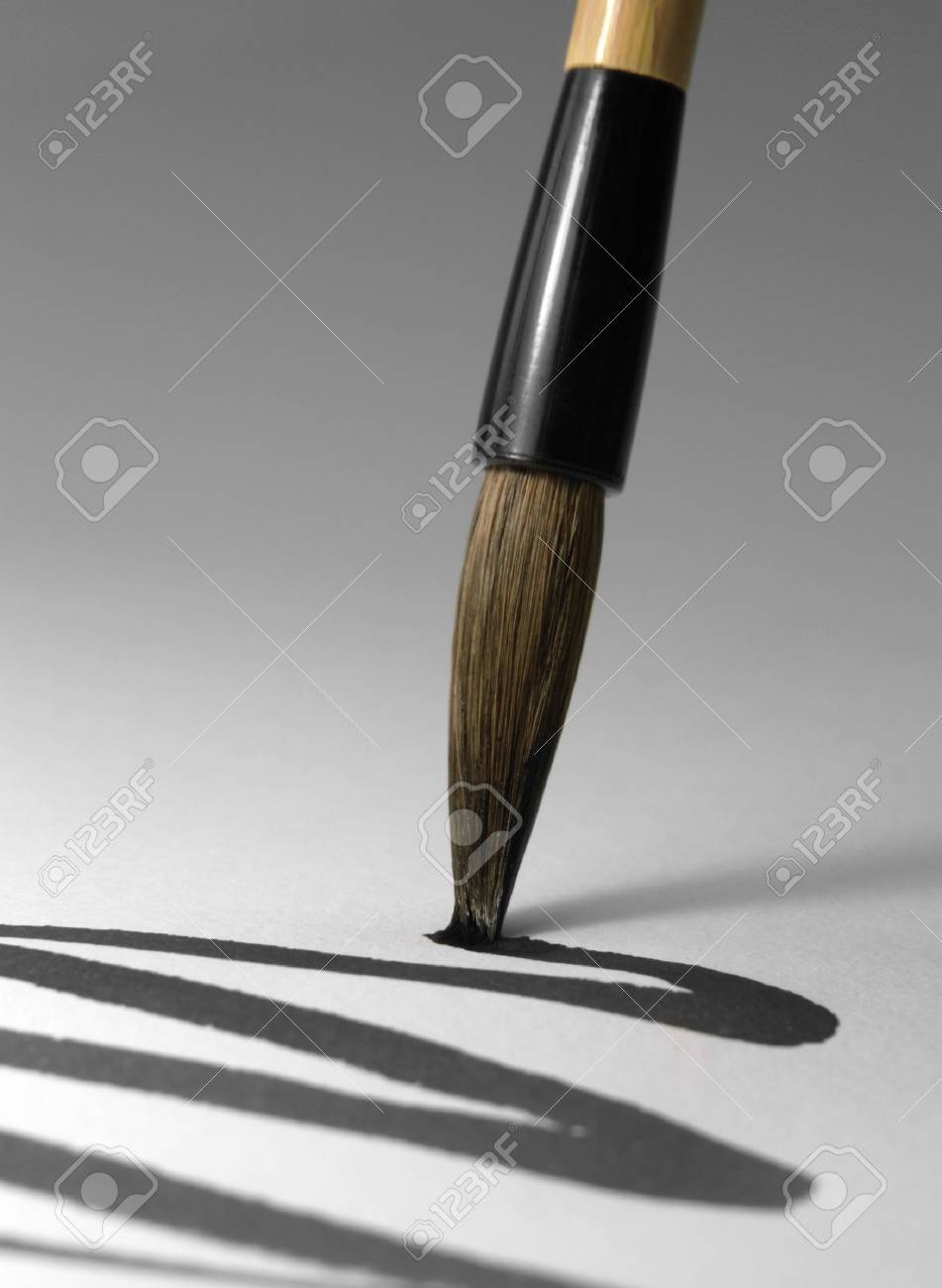 detail of a chinese brush while drawing a line in light back Stock Photo - 10987322