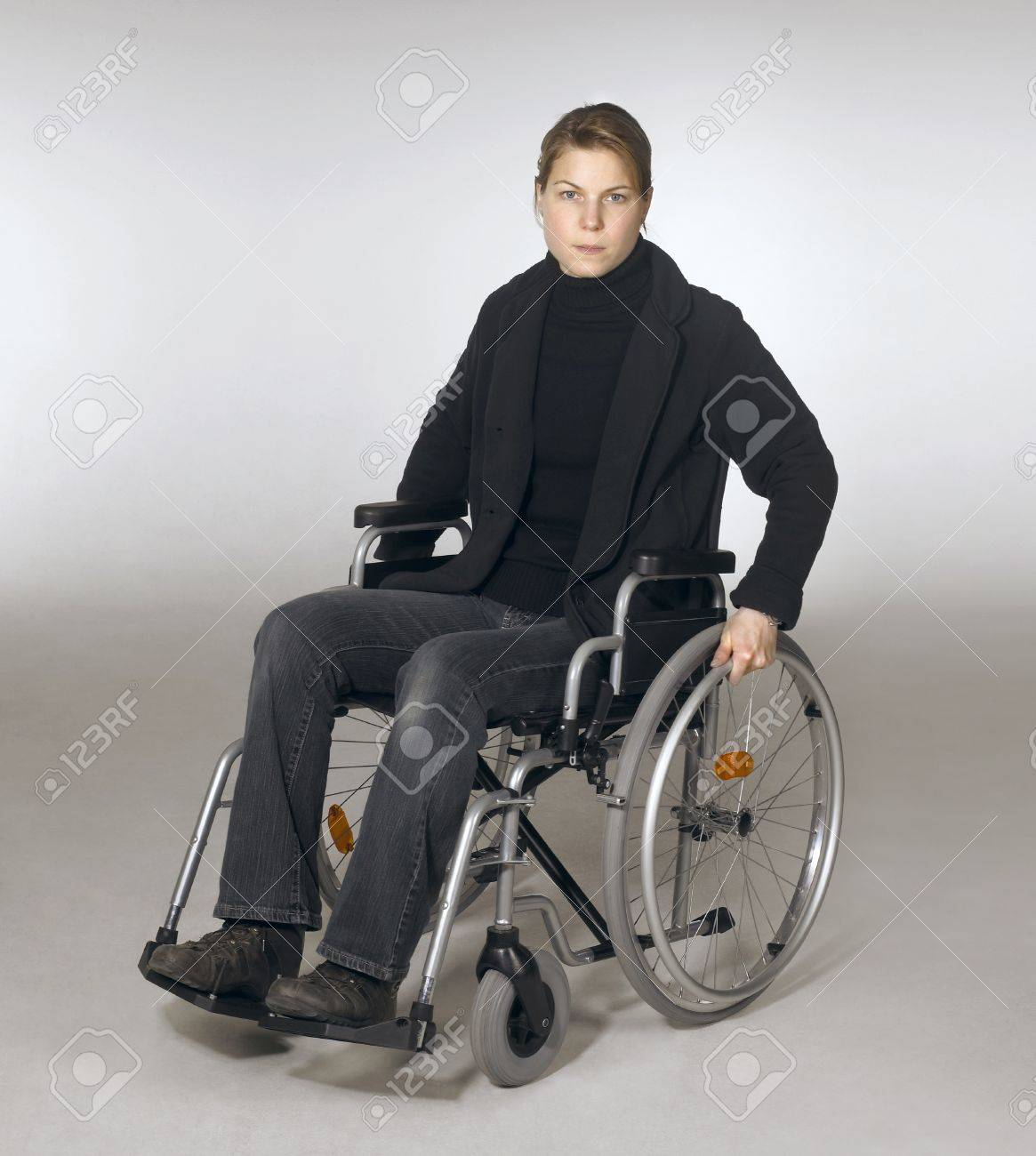 Young Person In Wheelchair - Stock photo studio photography of a young woman sitting in a wheelchair in light grey back