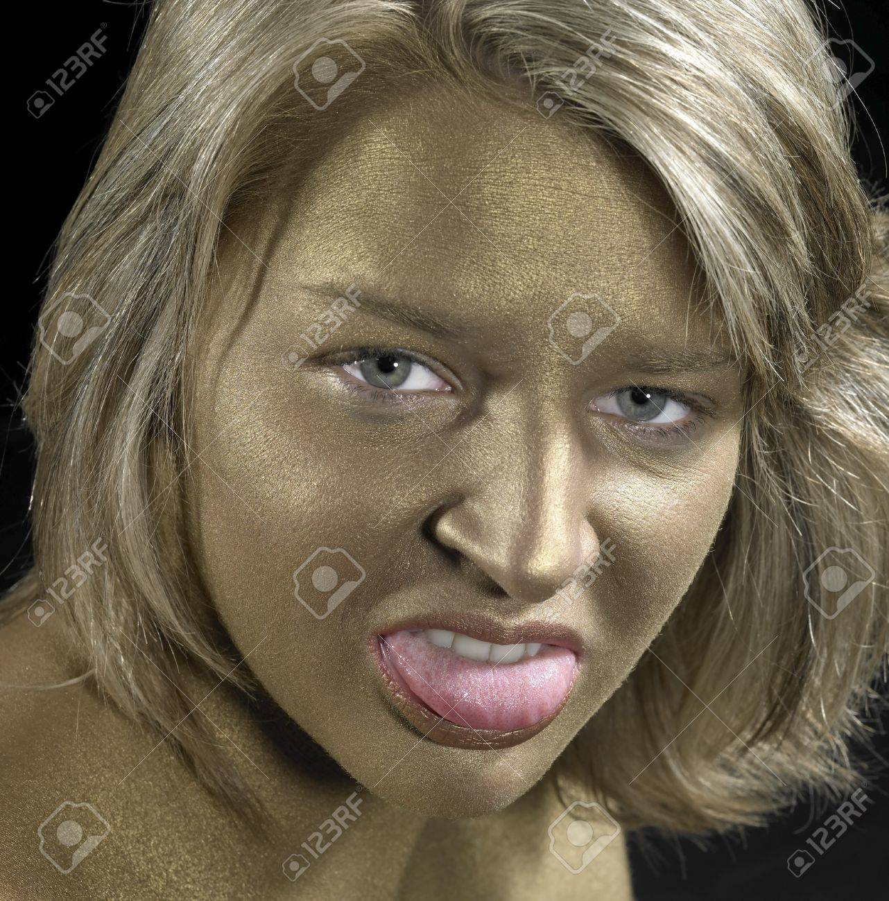 portrait of a angry young woman with golden bodypainted face Stock Photo - 11332969